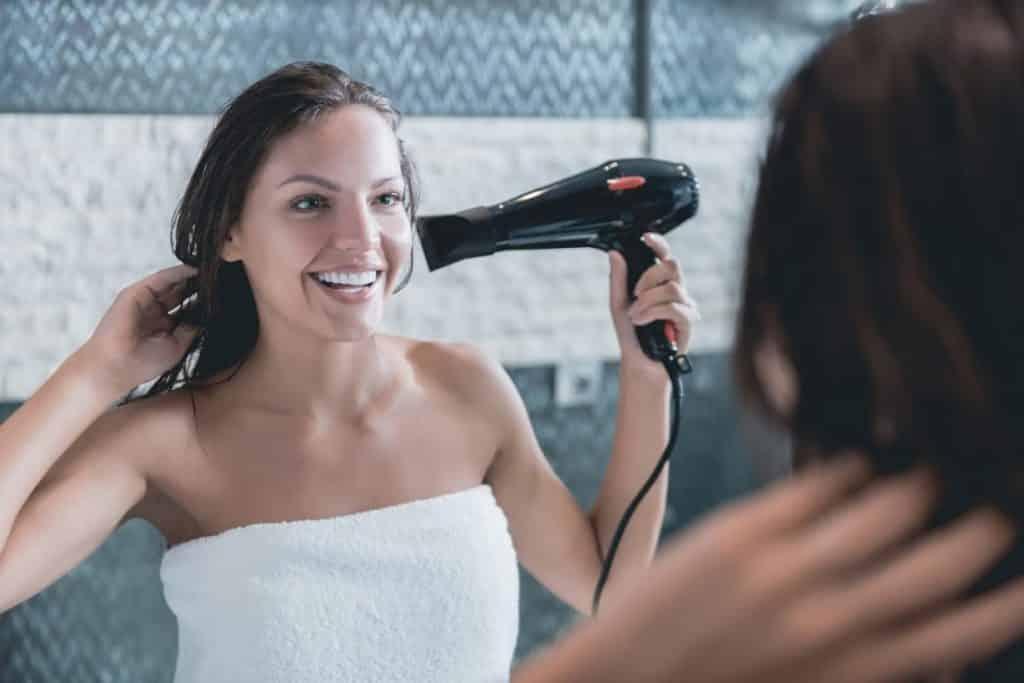 Mulher Secando Cabelo em Frente ao Espelho Sorrindo